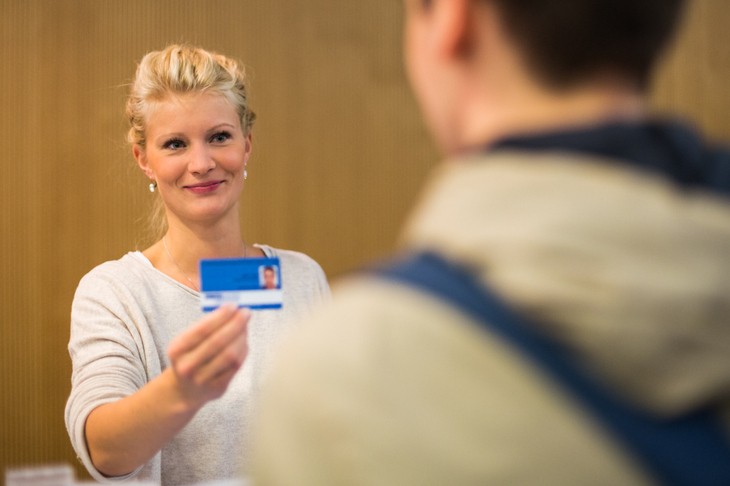 A Staff member gives a students his BlueCard